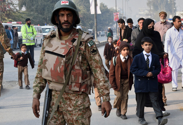A soldier stands guard as parents and children leave the site of the attack.