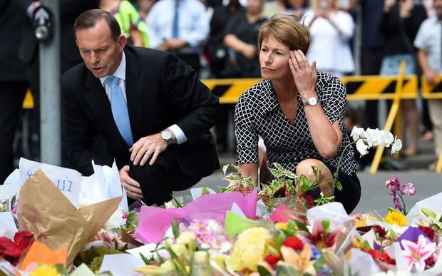 Prime Minister Tony Abbott and wife Margie join thousands of Sydneysiders to lay flowers near the cafe.
