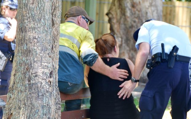 Police comfort a woman near the home in Manoora where the children were found dead.