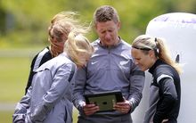 Football Ferns coach Tony Readings looks at video footage with his players