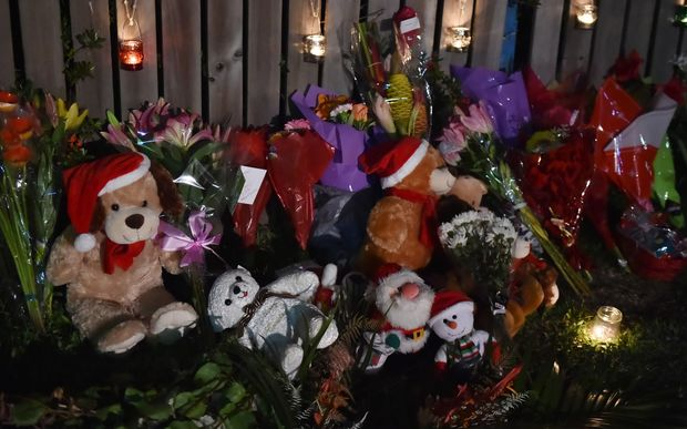 Flowers and stuffed toys near the scene where eight children were found dead in a house in Cairns, Australia.