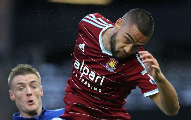 All White Winston Reid in action for West Ham twists to successfully head the ball.