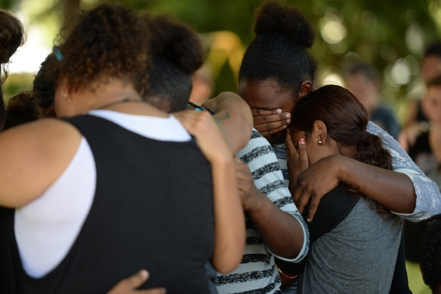 People comfort each other at the scene where the eight children were found.
