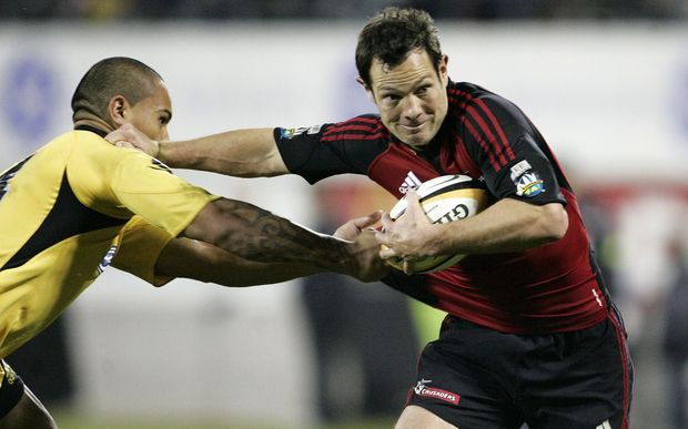 Leon MacDonald, with the Crusaders in 2008, fends off the Hurricanes' Hosea Gear.