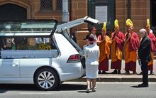 Buddhist monks pray as the coffin of Sydney siege victim Tori Johnson is placed in a hearse after his funeral.