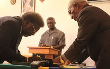 Solomon Islands finance minister Snyder Rini is sworn in by Governor General Sir Frank Kabui as Prime Minister Manasseh Sogavare looks on.