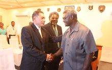 Solomon Islands Prime Minister Manasseh Sogavare congratulates Peter Shanel after taking his oath as Minister for Police. Looking on is the new finance minister Snyder Rini.