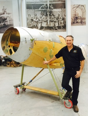 A photo of Gene DeMarco with a partly reconstructed Albatros DVa airplane