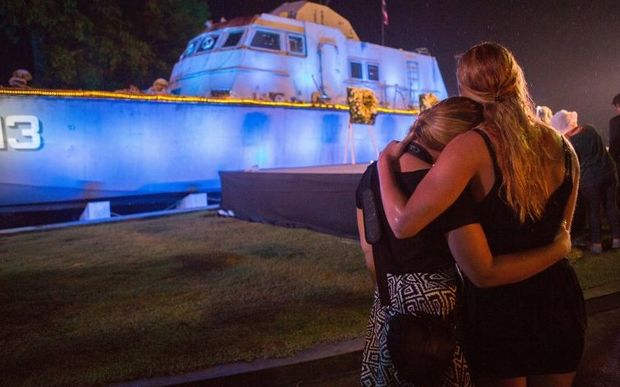 Two tourists comfort each other during a memorial service to mark the tenth anniversary of the Indian Ocean tsunami, in Phang-nga province.