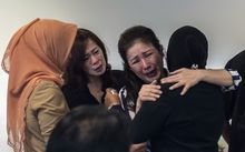 Family members of passengers from missing flight QZ8501 at the airport in Surabaya, East Java.