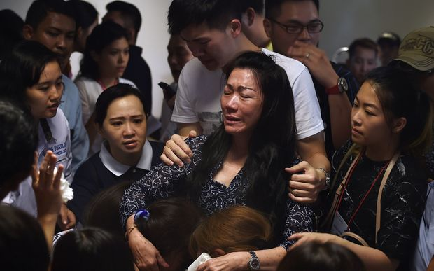 Family members of passengers onboard missing Malaysian air carrier AirAsia flight QZ8501 react after watching news reports showing an unidentified body floating in the Java sea.