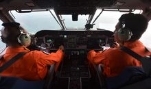 A pilot and co-pilot in the Indonesian air force keep a look out during search and rescue operations for the missing AirAsia flight QZ8501.