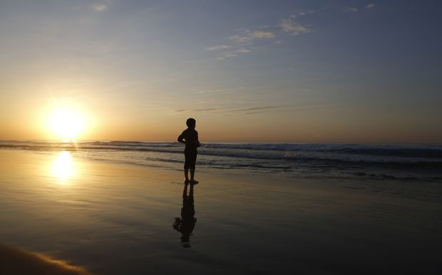 A Palestinian boy stands on the beach during the last sunset of 2014 off the coast of Gaza City.