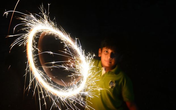 A Sri Lankan boy celebrates new year with a sparkler in Colombo.