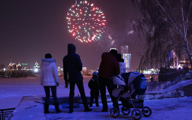 People watch fireworks displayed for the New Year celebrations over Ishim River in Kazakhstan capital city Astana.