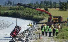 The car which crashed into the Wanganui River on the West Coast is removed from the water.