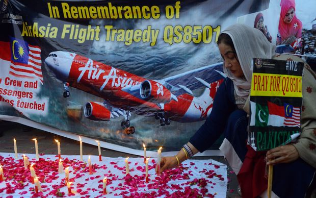 A Pakistani civil society activist places a candle during a vigil for the victims of AirAsia Flight QZ8501.