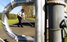 A security guard sweeps the road at the entrance to the Mangere Refugee Centre in Auckland.