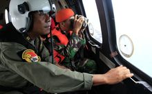 Indonesian crew members observe the surface of the sea during the search for AirAsia Flight QZ8501.
