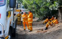 Volunteer fire fighters relax in the township of Gumeracha after fighting bush fires.