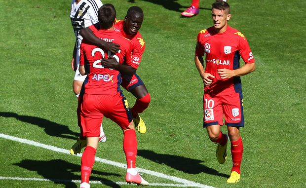 Adelaide United players celebrate a goal.