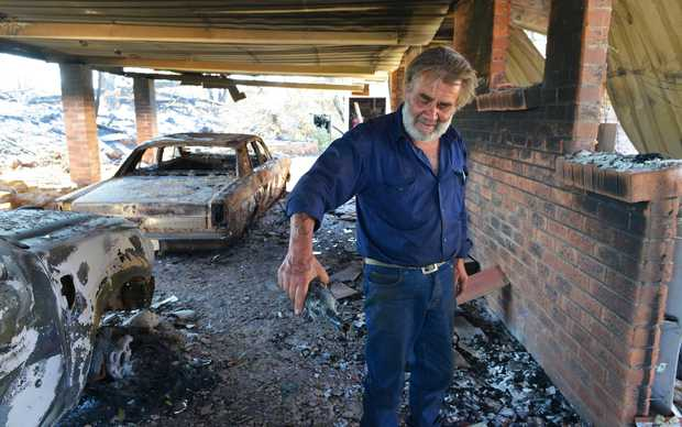 Resident David Miller pours the remains from a wine bottle that melted in the intensity of the heat when his home near Kersbrook was destroyed by a bushfire in the Adelaide Hills.