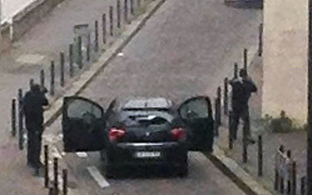 Armed gunmen face police officers near the offices of the French satirical newspaper Charlie Hebdo in Paris.
