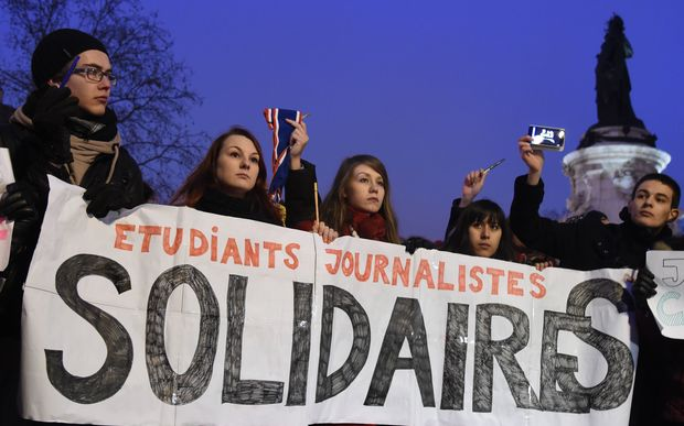 "Journalism students hold a banner reading in French: ""Journalism students : Solidarity"" as they raise pens during a gathering at the Place de la Republique."