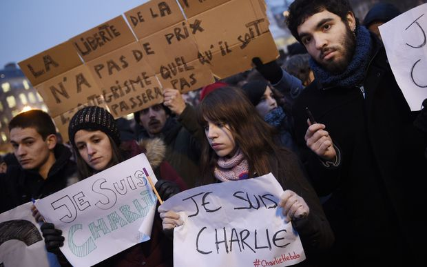 "A man holds a placard reading: ""Freedom of the press is priceless, fundamentalism, of any kind, will not pass"" as others hold up pens and placards reading in French, ""I am Charlie"" during a gathering at the Place de la Republique in Paris."