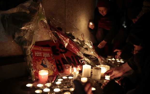 People light candles in front of an issue of Charlie Hebdo at the Place de la Republique, Paris.