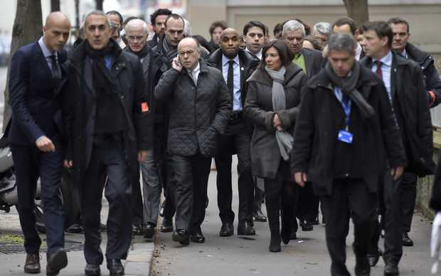 France's interior minister Bernard Cazeneuve (C, L) and Paris' Mayor Anne Hidalgo (C, R) arrive at the headquarters of the French satirical newspaper Charlie Hebdo.