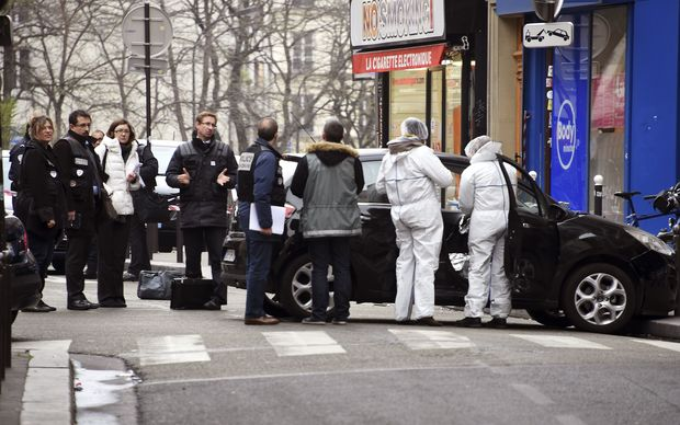 French police officers and forensic experts examine the car used by armed gunmen who stormed the Paris offices of satirical newspaper Charlie Hebdo.