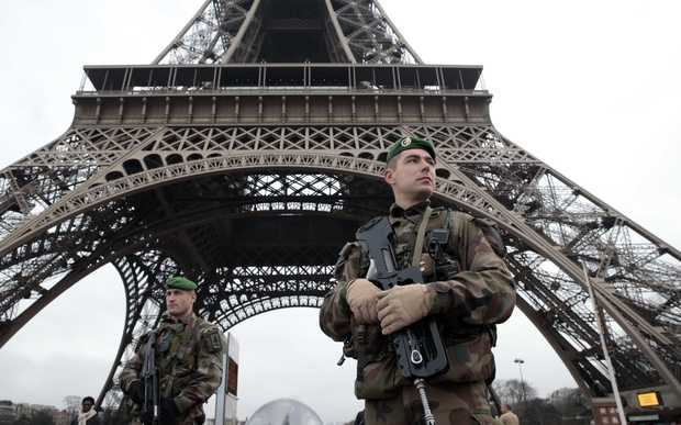 A French soldier in front of the Eiffel Tower as the capital is placed under the highest alert status.