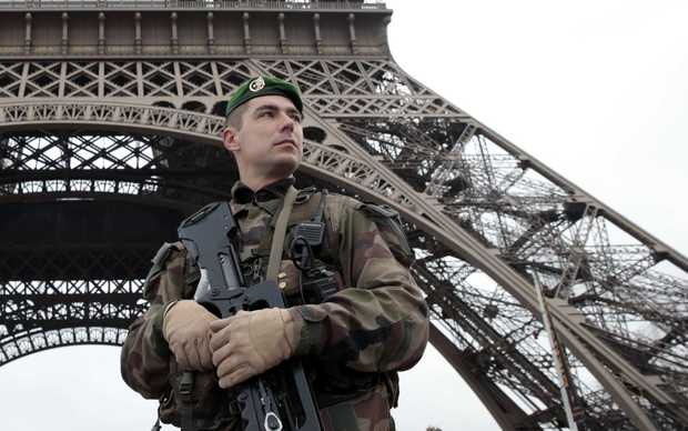 A French soldier in front of the Eiffel Tower as Paris is placed under the highest alert status.