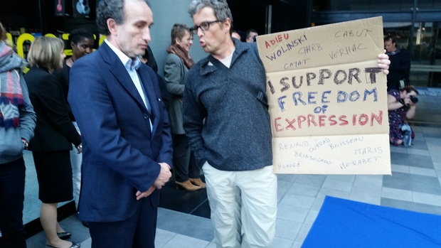 French ambassador Laurent Contini (left) talks with attendee at the Wellington vigil.