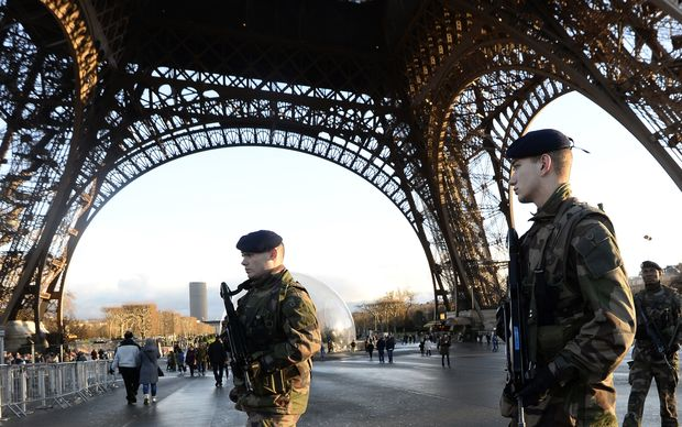 French soldiers patrol in front of the Eiffel Tower.