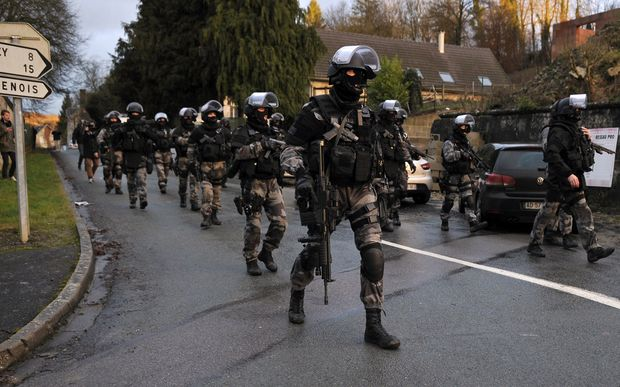 Members of the GIPN and RAID, French police special forces, walk in Corcy, northern France.