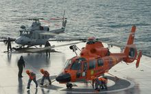 An Indonesian search and rescue helicopter lands on the deck of the Indonesian Navy vessel KRI Banda Aceh as operations to lift the tail of AirAsia flight QZ8501 continue.