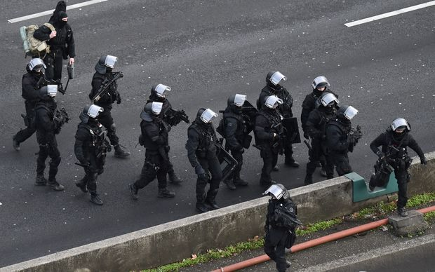"Members of the French police special force RAID walk on the ""peripherique"" (circular road) before taking their positions."
