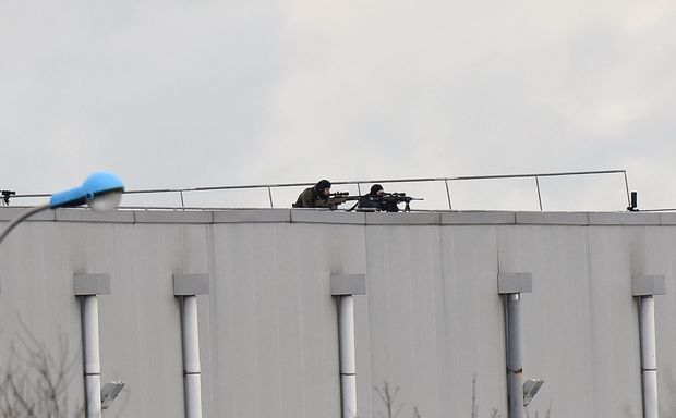 Police marksmen take up a position on a roof in Dammartin-en-Goele, north-east of Paris.