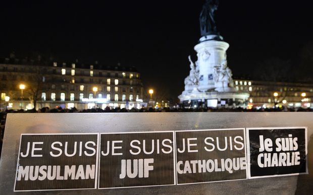 "People hold a placard reading ""I am Muslim, I am Jewish, I am Catholic, I am Charlie"" during a Paris rally."