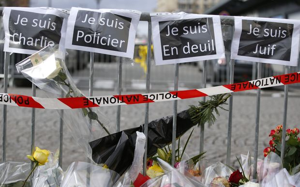 "Flowers and signs that read, ""Je suis Charlie"", ""I am police"", ""I am mourning"", I am Jewish"", near a kosher grocery store in Porte de Vincennes, eastern Paris."