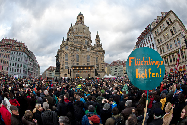 "A sign reading ""Help the refugees!"" in the foreground as thousands of people take part in a rally themed: ""For Dresden, for Saxony - living together in the sense of a global awareness, humanity and dialogue""."