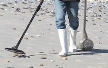 Man with metal detector on beach