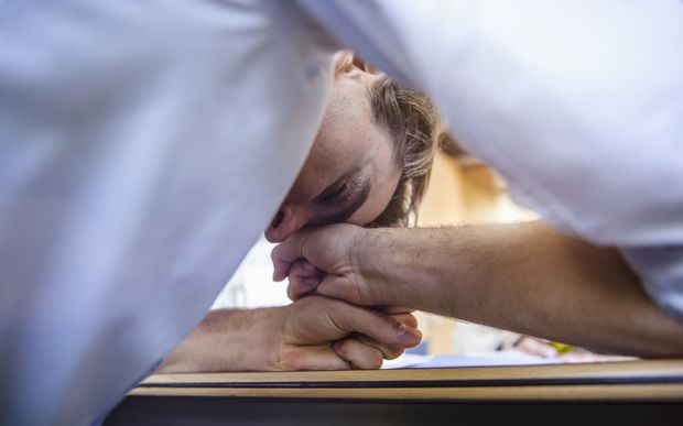 Office worker head down exhausted on table (file photo)