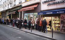 People wait outside a newsagents in Paris as the latest edition of French satirical magazine Charlie Hebdo goes on sale.