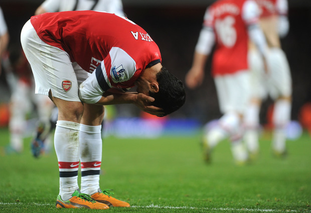 Arsenal's Mikel Arteta holds his head in dejection.