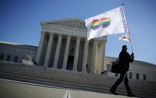An activist from Equality Beyond Gender holds a marriage pride flag outside the U.S. Supreme Court January 2015.