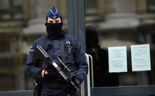 An armed policeman stands guard at the entrance of Belgium's federal prosecutor office in Brussels.