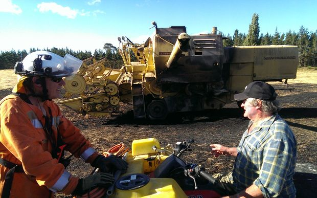 Volunteer firefighter Paul Fiddymont (left) talks to Michael Manion whose combine harvester sparked caused the fire.